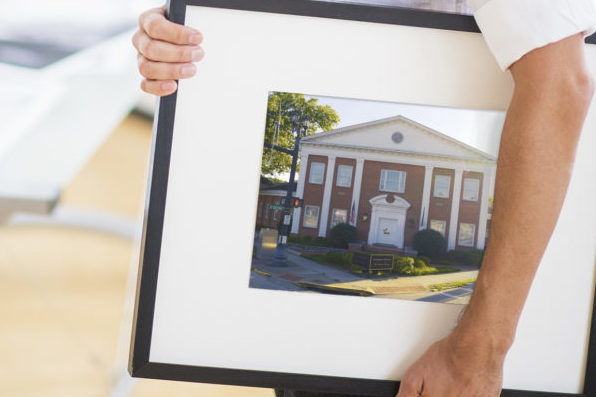 Portrait of man holding photo of IH building