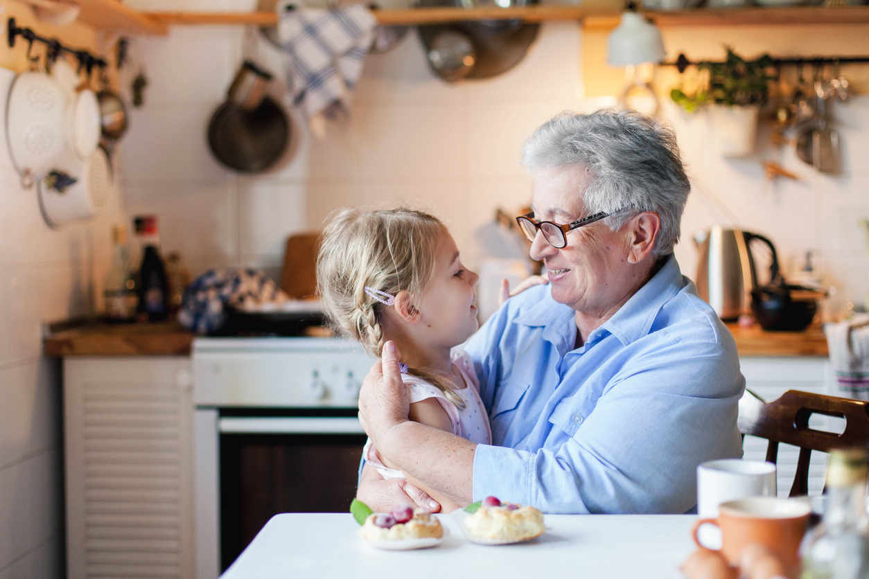 Happy grandmother is hugging granddaughter in cozy home kitchen. Senior woman and cute little child girl are smiling.