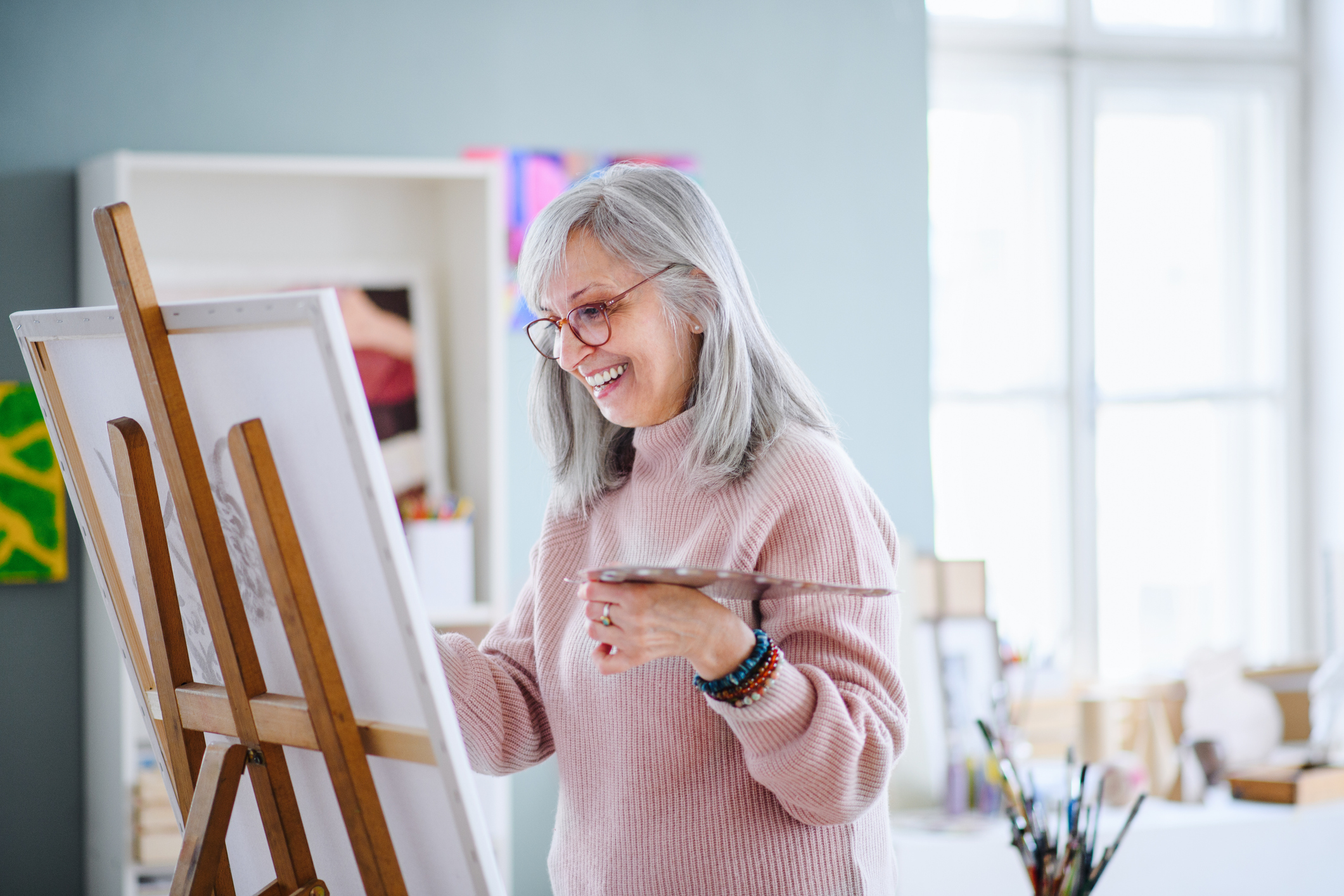Senior woman painting pictures in art class.